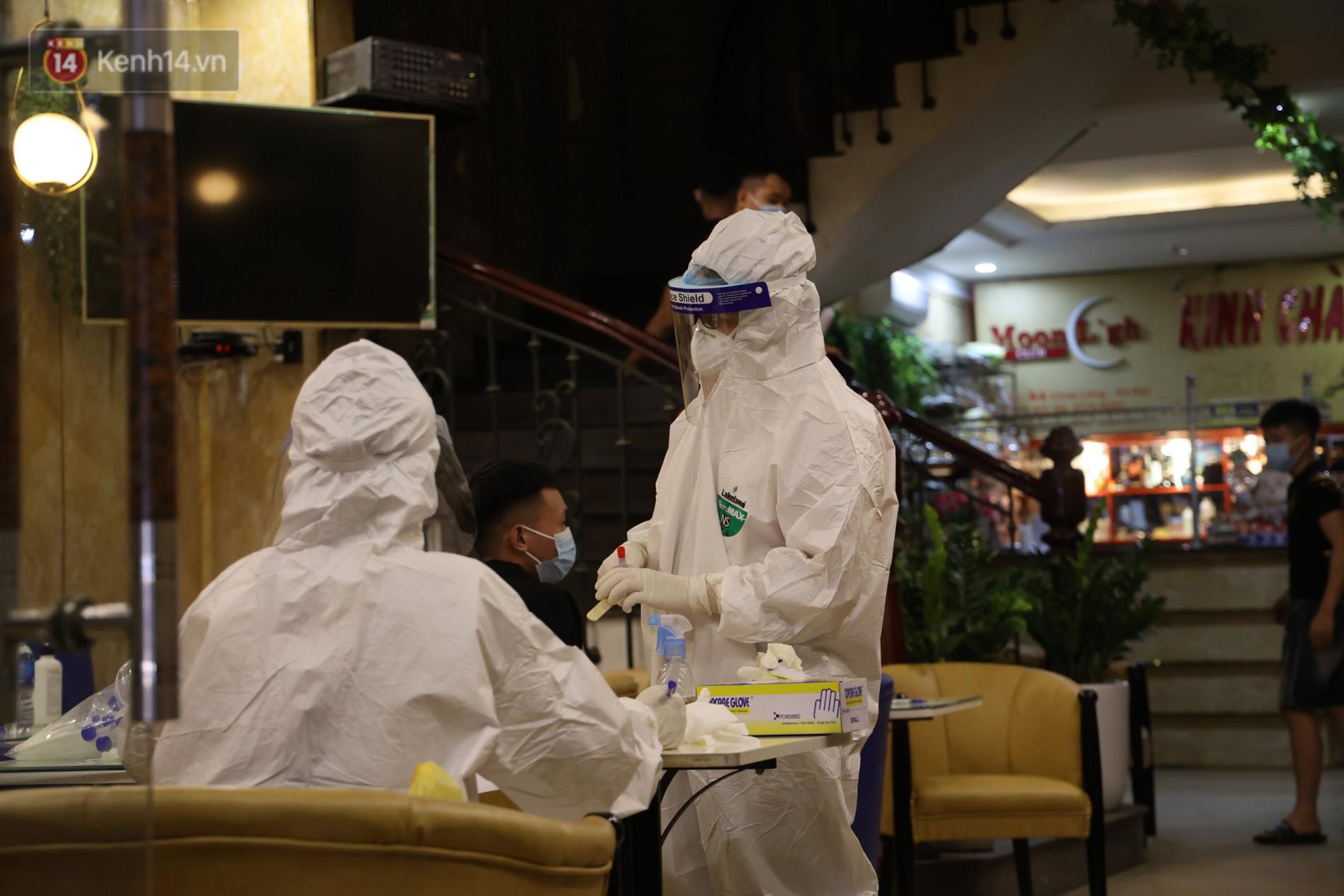 Ảnh: Lấy mẫu xét nghiệm nhân viên, phun khử khuẩn quán karaoke nơi nam bác sĩ dương tính với SARS-CoV-2 từng đến - Ảnh 6.
